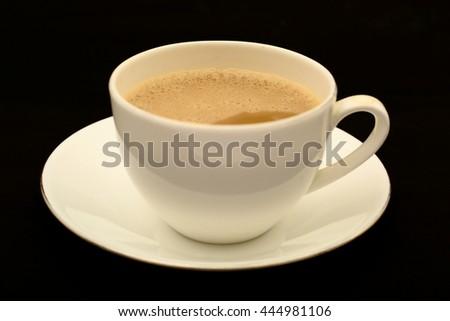 Cup of milk tea in black background. - stock photo