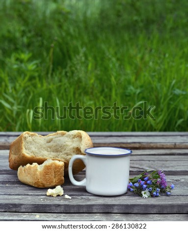 Cup of milk with bread and bunch of flowers on wooden planks over green grass background, rural summer still life - stock photo