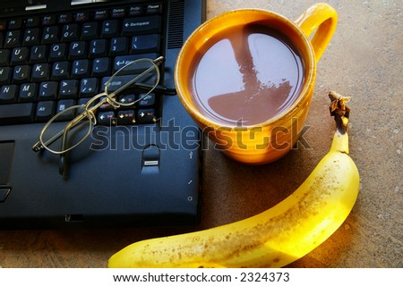 Cup of morning coffee with laptop and a banana - stock photo