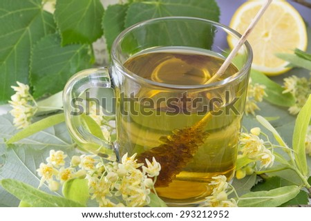 Cup of natural lime tea with sugar stick, lemon and lime flowers