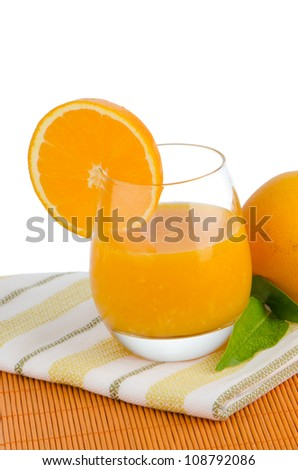 Cup of orange juice and fresh orange as a background