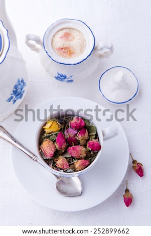 Cup of pink rose buds like tea and sugar bowl with brown sugar and teapot on light background - stock photo