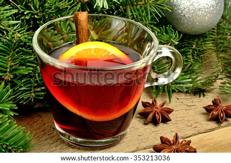 Cup of red wine with orange fruit and cinnamon on table