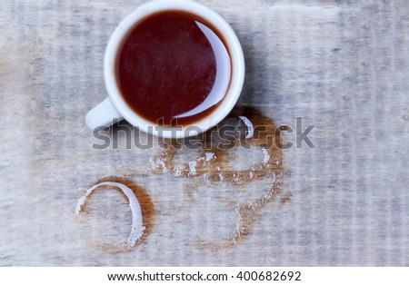 cup of spilled coffee on a wooden surface.view from above - stock photo