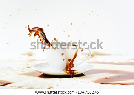 Cup of spilling coffee creating beautiful splash with stains on white. Coffee break, breakfast concept.  - stock photo