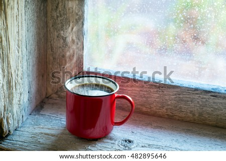 cup of steaming coffee on a window sill