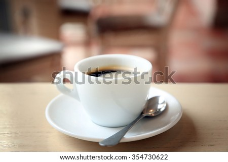 Cup of tasty coffee with spoon in cafe
