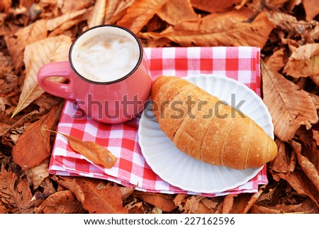 Cup of tasty hot drink and fresh croissant on napkin, on autumn leaves background