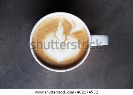 Cup of tasty latte is standing on the grey textured table. There is nice picture is painted on the top of the latte. Latte is in the white big cup. - stock photo