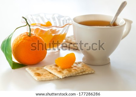 cup of tea and biscuits and tangerine slice - stock photo