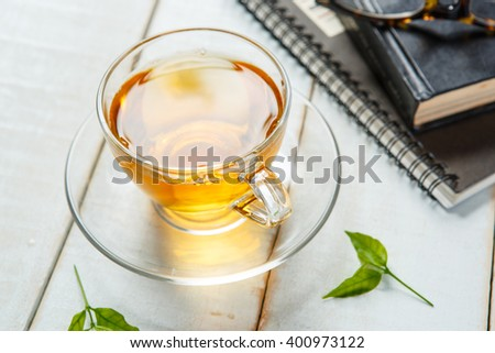 Cup of tea and book on white wooden table