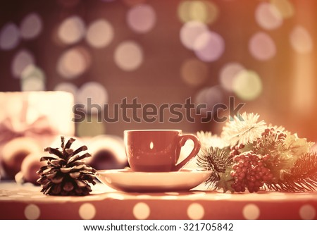 Cup of tea and branch with Christmas lights on background. - stock photo