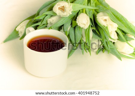 Cup of tea and bunch of spring tulips on the table. Shallow depth of field. Selective focus. Toned. - stock photo