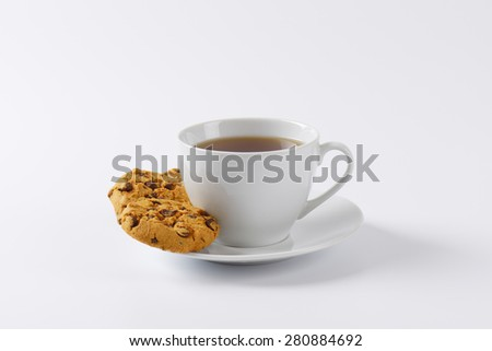cup of tea and chocolate chip cookies on white background - stock photo