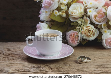 Cup of tea and couple of rings on wooden table with flowers, still life - stock photo