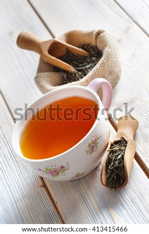 Cup of tea and dried tea leaves on wooden table