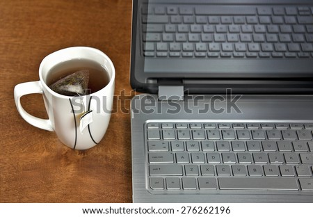 cup of tea and laptop on wooden desk