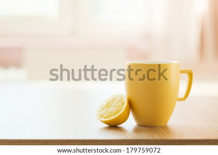 Cup of tea and lemon closeup with sunny house interior in background - stock photo