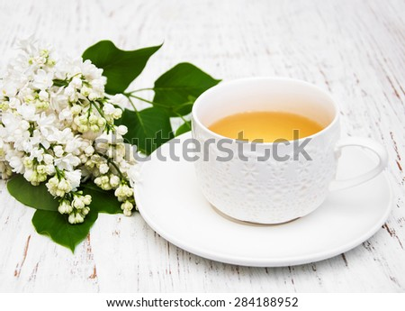 Cup of tea and lilac flowers on a old wooden background