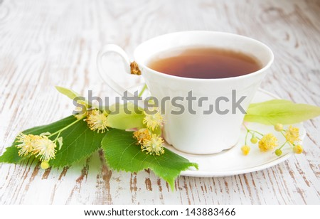 cup of tea and linden flowers on a wooden background
