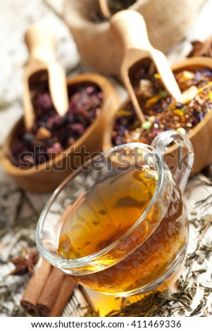 Cup of tea and mix of assorted tea leaves  - stock photo