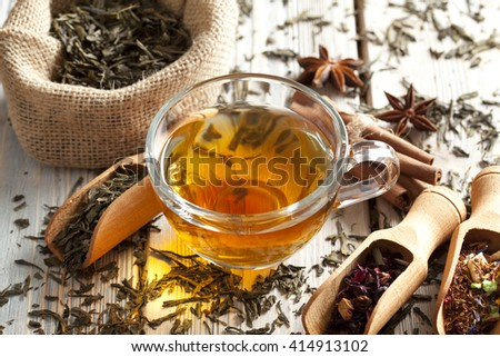 Cup of tea and mix of assorted tea leaves on wooden table