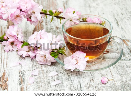 Cup of tea and pink sakura blossom on a old wooden background - stock photo