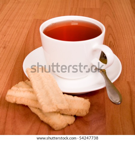 cup of tea and some cookies on wooden table - stock photo