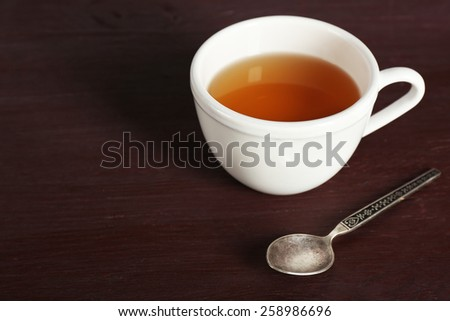 Cup of tea and spoon on color wooden table background - stock photo