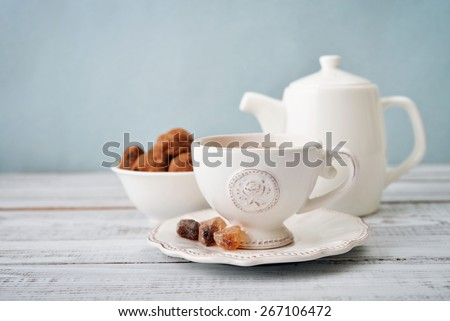 Cup of tea and sugar with cookies  over blue background - stock photo