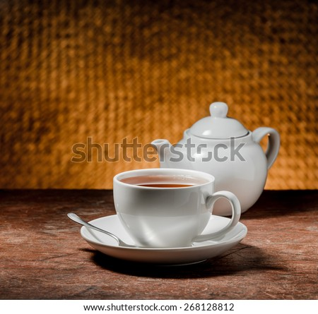 cup of tea and teapot on a wooden table - stock photo