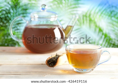 Cup of tea and teapot on nature background