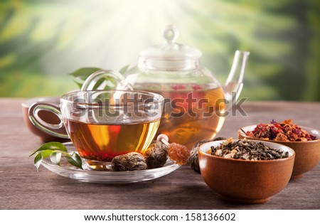 Cup of tea and teapot with blooming tea on blur green background - stock photo