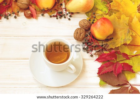 cup of tea, apples, pears, nuts and autumn yellow and red leaves. autumn breakfast. selective focus, toned photo