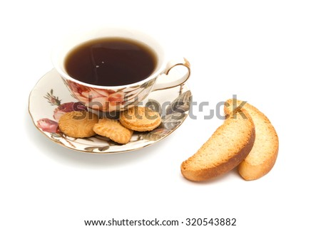 cup of tea, cookies and pair of crackers on white background - stock photo