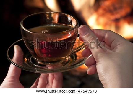 cup of tea in his hands against the backdrop of fire in the fireplace - stock photo