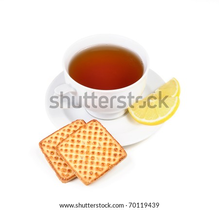 Cup of tea, lemon and some cookies on white dish - stock photo