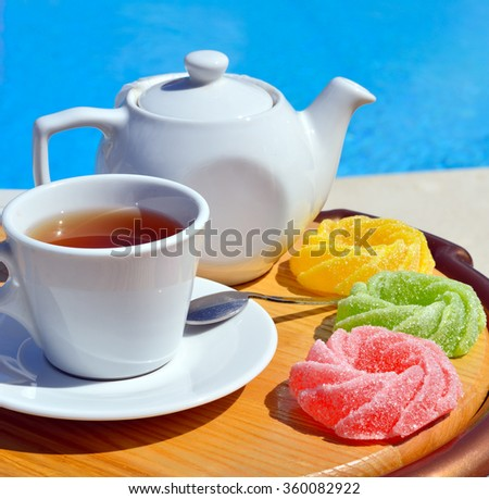 Cup of tea on a sauce, teapot and colored marmalade beside the pool.