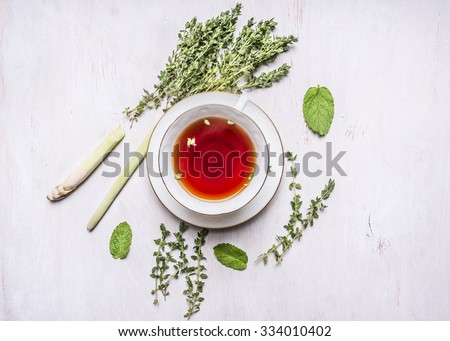 cup of tea on a saucer with a set of herbal tea thyme, mint, lemon grass on wooden rustic background top view close up - stock photo