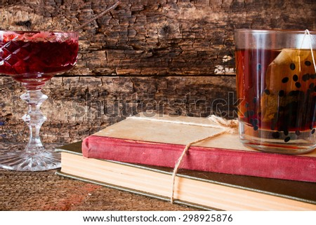 cup of tea on a stack of books next to a rope tied to jam in a vase