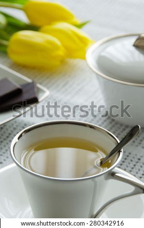 Cup of tea on the plate and spoon with flowers and sugar-bowl on the table with tablecloth