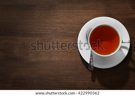 Cup of tea on wooden table - stock photo