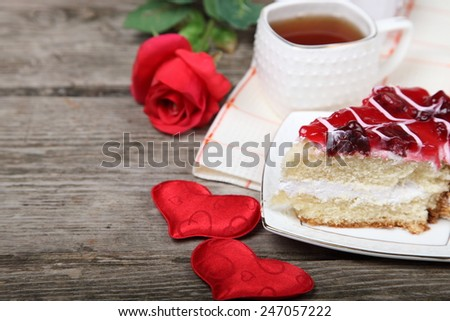 Cup of tea, piece of cake and red heart on wooden background. Valentines day background. - stock photo