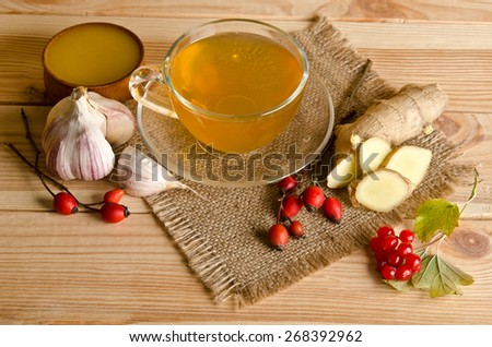 Cup of tea,slices of ginger,honey,rosehip berries and viburnum on a wooden table - stock photo
