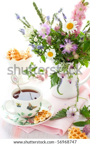Cup of tea,waffles and summer flowers - stock photo