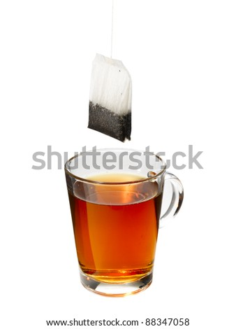 Cup of tea with a teabag hanging above it. - stock photo