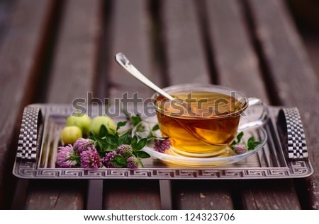Cup of tea with apples and pink clover - stock photo