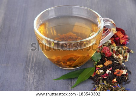 Cup of tea with aromatic dry tea on wooden background - stock photo