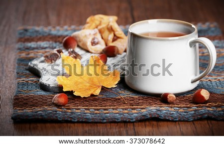 Cup of tea with autumn decor on wooden table.