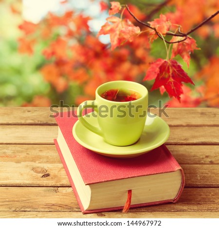 Cup of tea with autumn leaves reflection on book on wooden table - stock photo